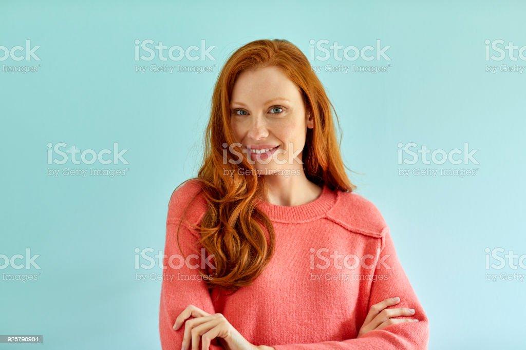 Lächelnde Frau stehend vor blauem Hintergrund – Foto