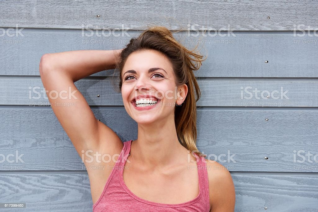 Smiling woman standing by wall with hand in hair stock photo