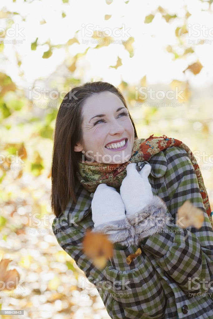 Smiling woman standing in falling autumn leaves royalty free stockfoto