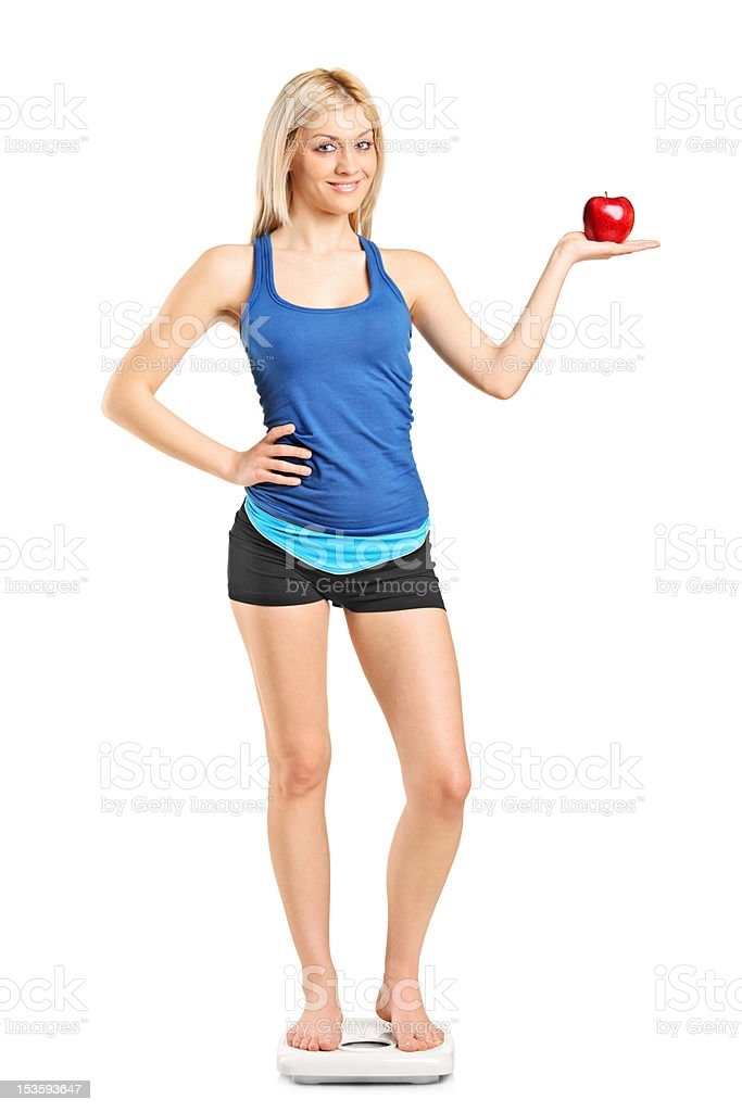 Smiling woman standing on a weight scale royalty-free stock photo