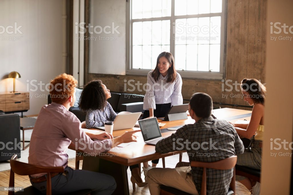 Smiling woman standing to address colleagues at a work meeting stock photo