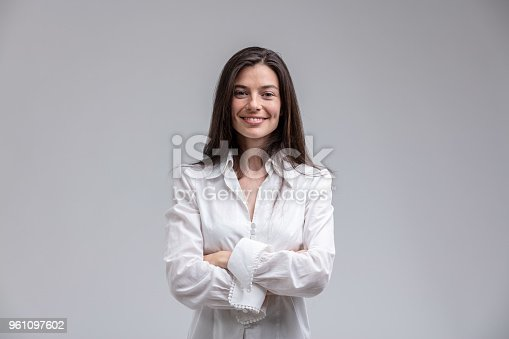 Portrait of long-haired brunette cheerful woman wearing white shirt standing with arms crossed