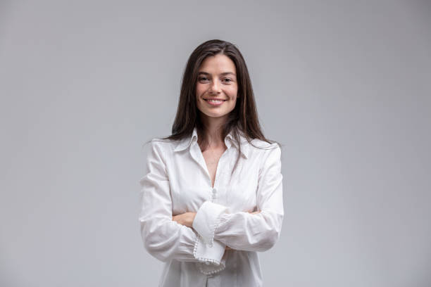 Smiling woman standing with arms crossed Portrait of long-haired brunette cheerful woman wearing white shirt standing with arms crossed waist up stock pictures, royalty-free photos & images