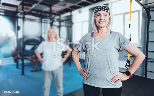 936573360 istock photo Smiling woman standing with hands on hips at gym 936572946