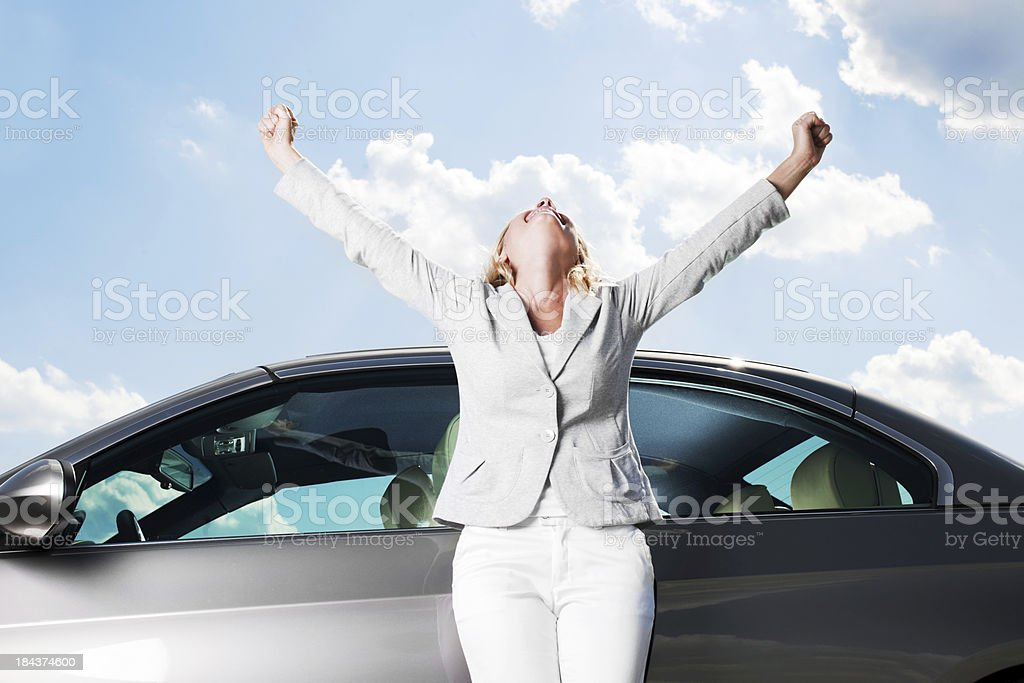 Smiling woman stretches arms toward sky in victory stock photo