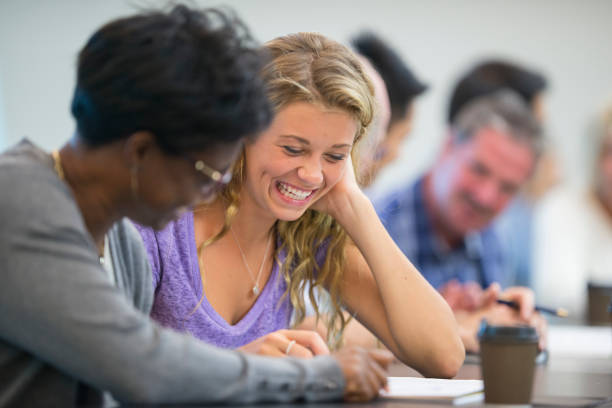 Smiling woman studying A smiling blonde woman looks at a notebook which an older black woman is writing in. They are seated at a table with other students behind them. adult learning stock pictures, royalty-free photos & images
