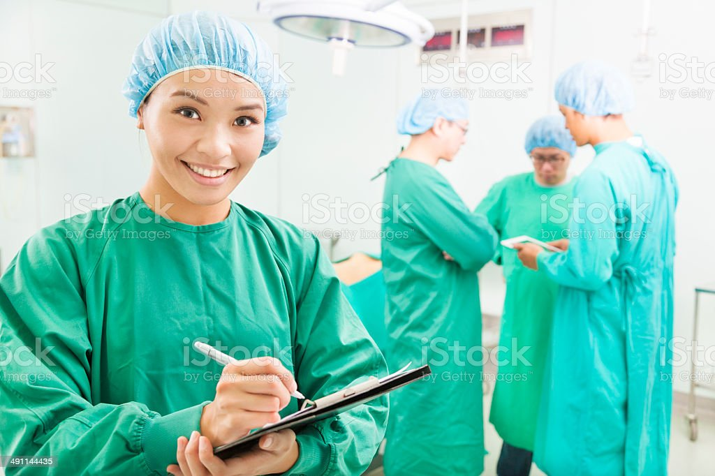 Smiling woman surgeons writing patient operating records stock photo