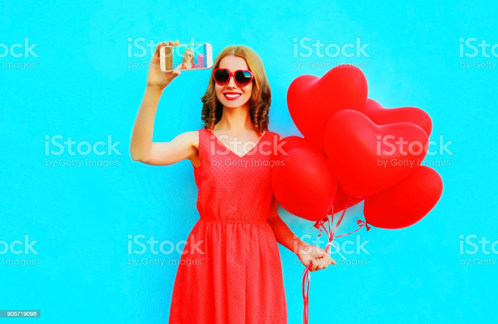 smiling woman takes a picture self portrait on a smartphone holds an air balloons on blue background stock photo