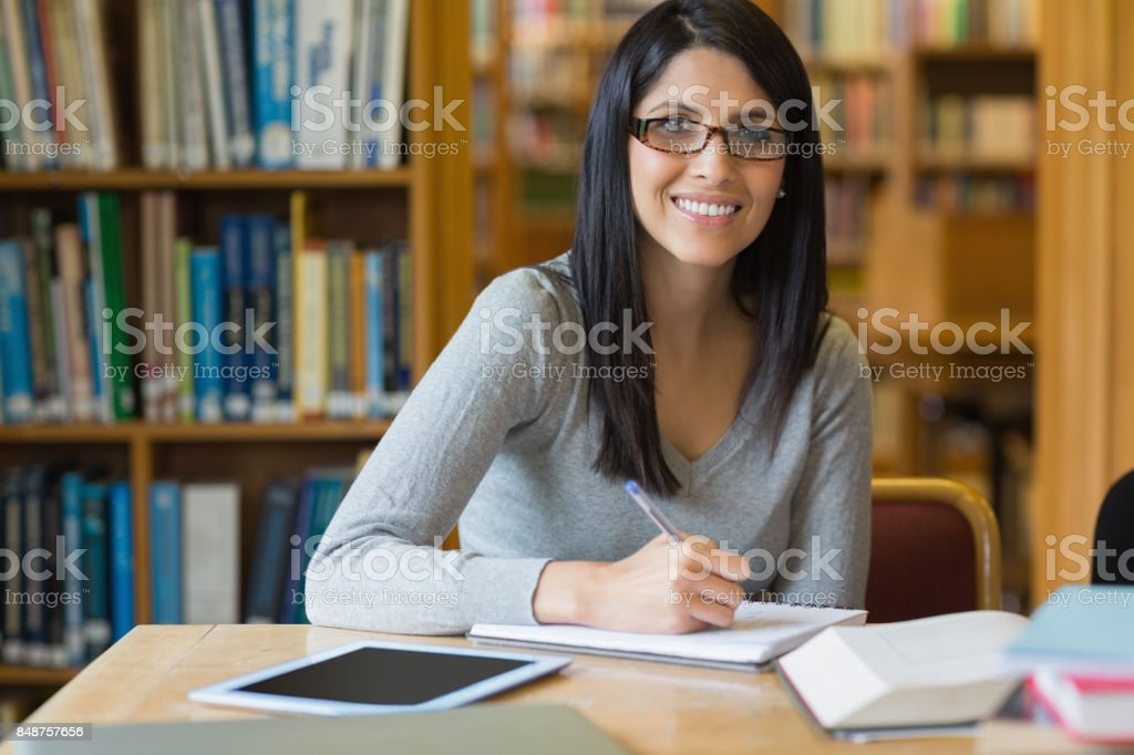 Leende kvinna anteckningar medan du gör forskning bildbanksfoto