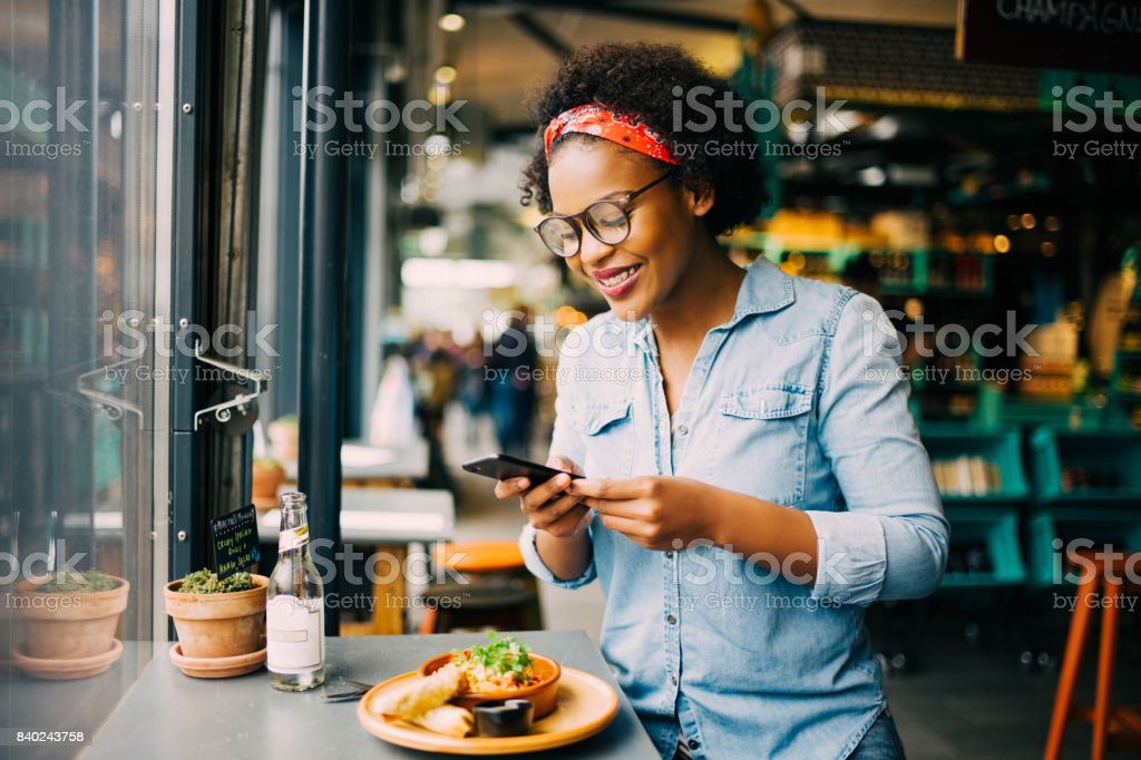 Smiling woman taking photos of her food in a cafe stock photo