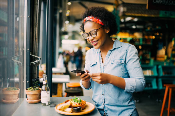 smiling woman taking photos of her food in a cafe - foodie stock photos and pictures