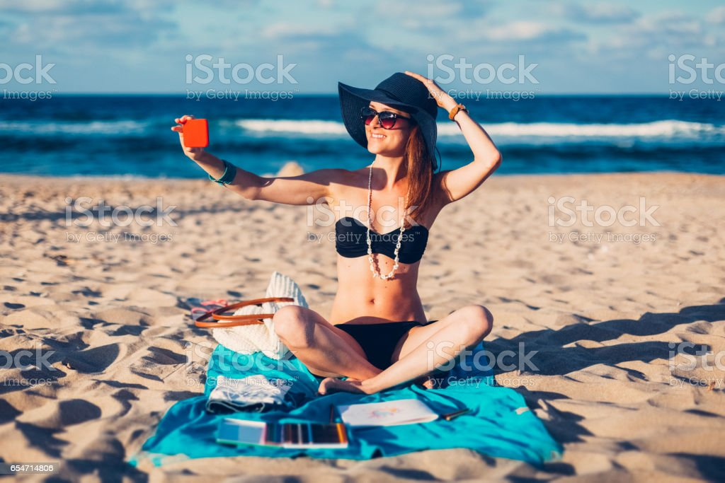 Smiling woman taking selfie at the beach stock photo