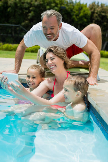 lächelnde frau nehmen selfie mit familie im schwimmbad - senior bilder wasser stock-fotos und bilder