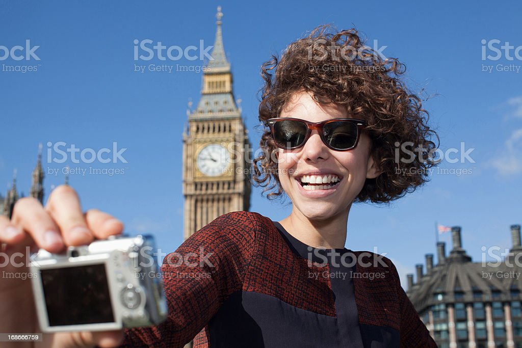 Smiling woman taking self-portrait with digital camera below Big Ben clocktower royalty-free stock photo