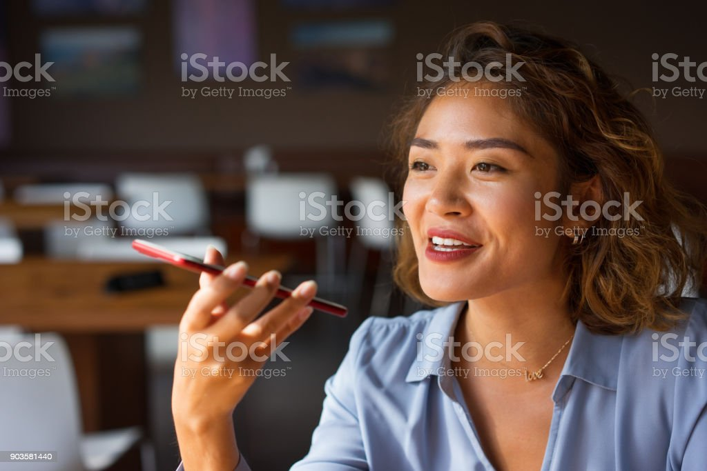 Smiling Woman Talking on Phone with Loudspeaker stock photo
