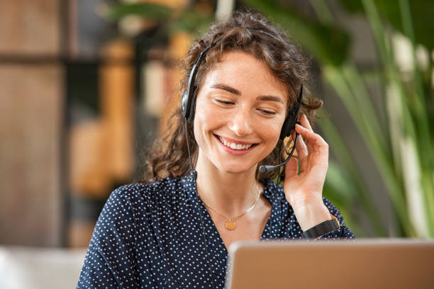 Smiling woman talking to customer on headphones stock photo