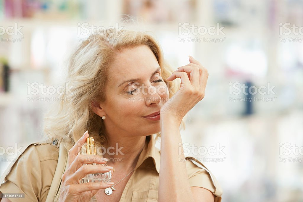 Smiling woman testing perfume in store stock photo