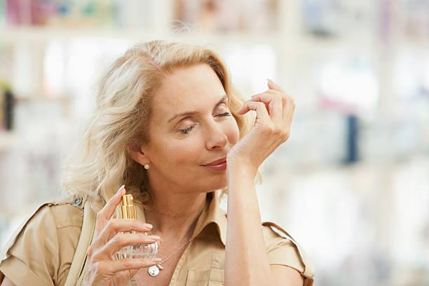 smiling woman testing perfume in store - parfym bildbanksfoton och bilder