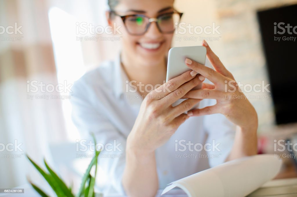Smiling woman texting message while working at home royalty-free stock photo