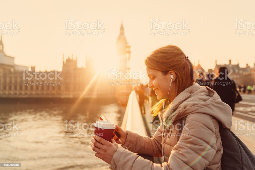 Smiling woman texting near the Thames river stock photo