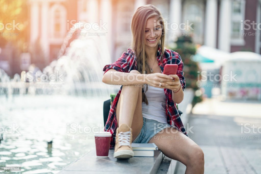 Smiling woman texting on her mobile phone in the city royalty-free stock photo