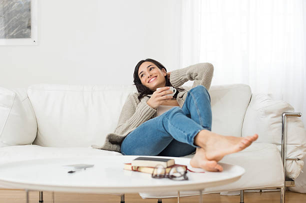 smiling woman thinking on sofa - taking a break stock photos and pictures