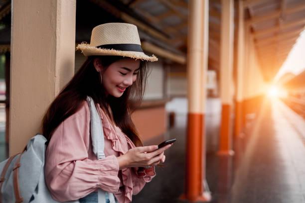 Lächelnde Frau Reisende mit Rucksack halten Smartphone auf Urlaub Entspannung am Bahnhof,Entspannungskonzept, Reisekonzept