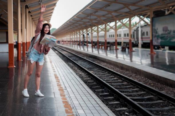 Lächelnde Frau Reisende mit Rucksack halten Weltkarte Planung Urlaub Entspannung am Bahnhof,Entspannungskonzept, Reisekonzept