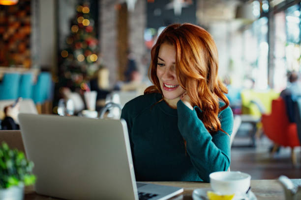 Smiling woman typing on laptop at cafe stock photo