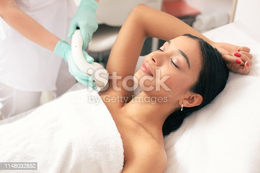 istock Smiling woman undergoing laser hair removal on her armpit 1148032852