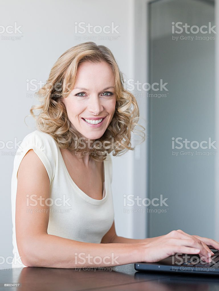 Smiling woman using a laptop computer royalty-free stock photo