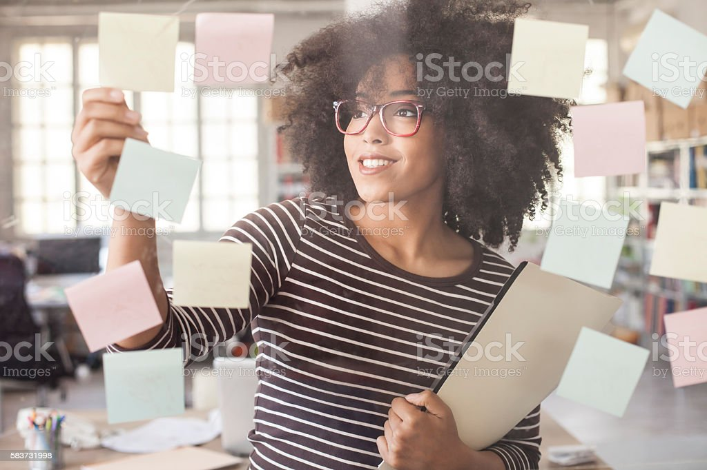 Smiling woman using adhesive notes in modern office – Foto