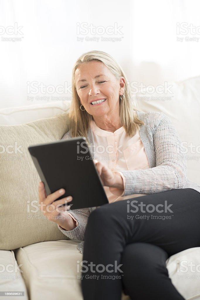 Smiling senior woman using digital tablet while sitting on sofa at...