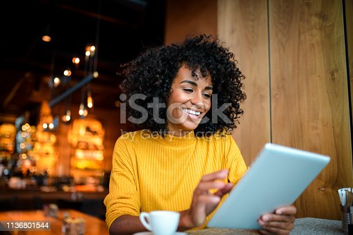 istock Smiling woman using digital tablet. 1136801544