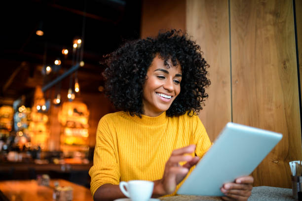Smiling woman using digital tablet. Beautiful smiling African American woman using digital tablet at the bar. brazilian ethnicity stock pictures, royalty-free photos & images