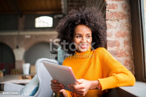 istock Smiling woman using digital tablet. 943023040