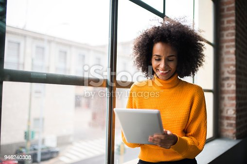 Smiling African American woman using digital tablet at the work.