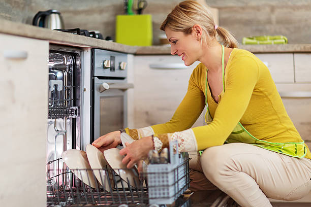 Smiling woman using dishwasher in the kitchen. Happy young woman crouching and using dishwasher in the kitchen. dishwasher stock pictures, royalty-free photos & images