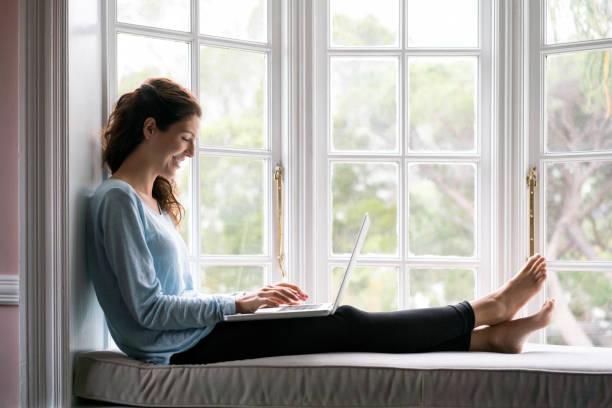 Lächelnde Frau mit Laptop am Nischen Fenstersitz – Foto