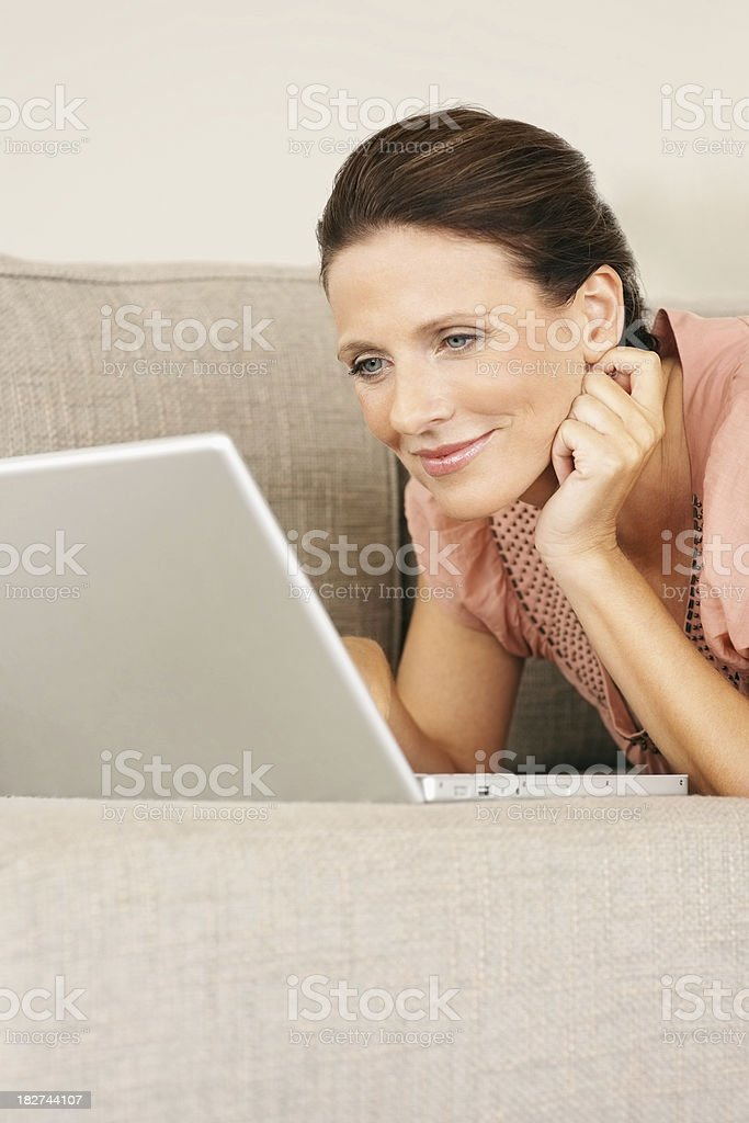 Smiling woman using laptop at home royalty-free stock photo