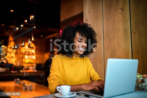 istock Smiling woman using laptop at the bar. 1135176767