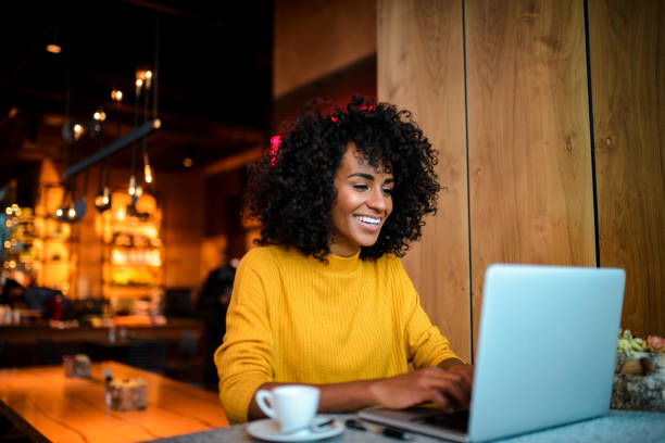 Smiling woman using laptop at the bar. Beautiful smiling African American woman using laptop at the bar. using computer stock pictures, royalty-free photos & images