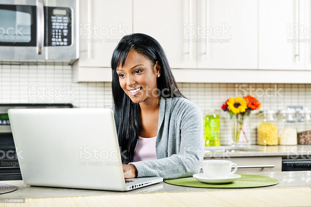 Smiling woman using laptop next to coffee cup in kitchen royalty-free stock photo