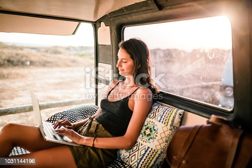 Freelance woman working from the van while taking a road trip
