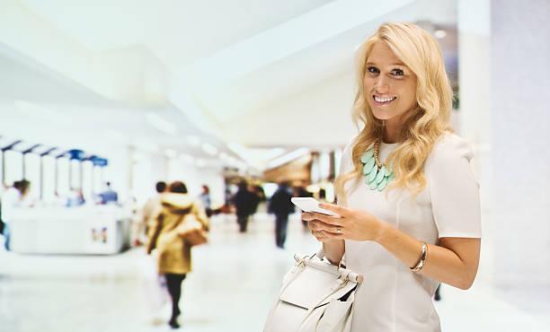lächelnde frau mit handy in der shopping mall - canda armband stock-fotos und bilder