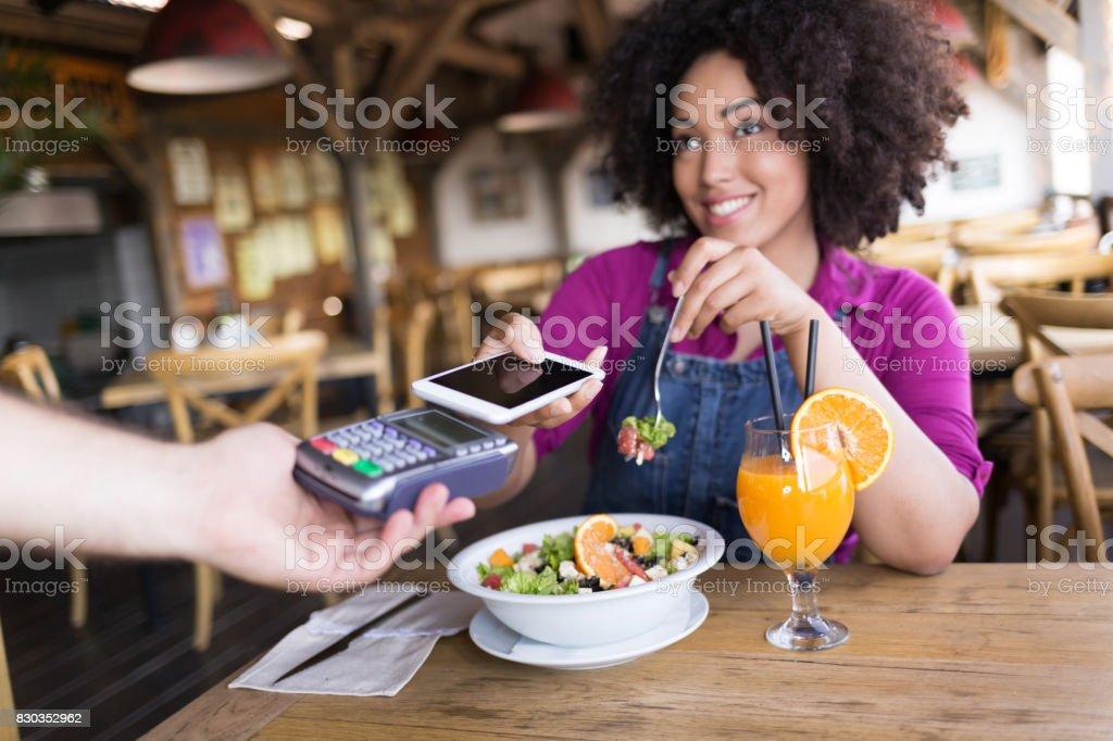 Femme souriante, à l'aide de paiement mobile dans restaurant - Photo