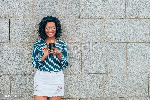 616898108istockphoto Smiling woman using mobile phone. 1162006312