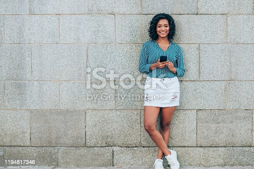 616898108istockphoto Smiling woman using mobile phone. 1194817346