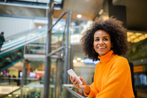 smiling woman using mobile phone. - online shopping imagens e fotografias de stock