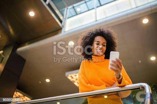 istock Smiling woman using mobile phone. 933501900